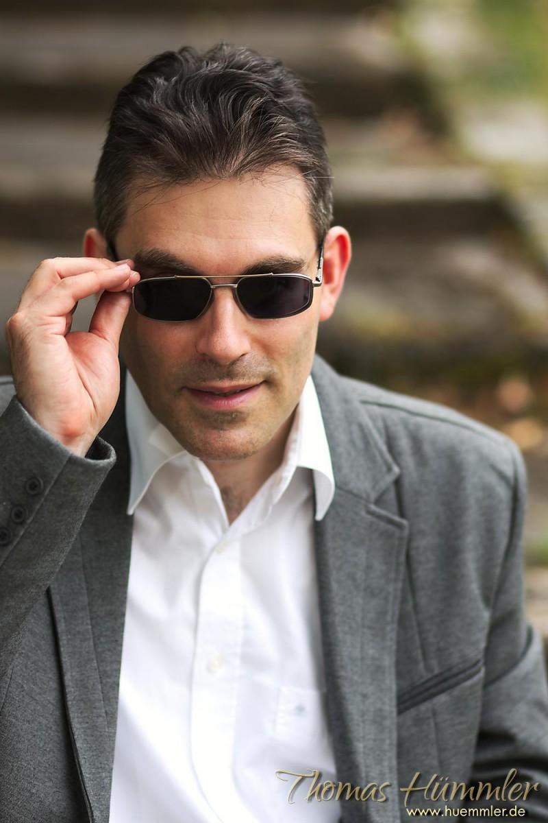 Dynamisch und cool: Der Griff zur Sonnenbrille bringt Bewegung ins Bild. Es ist bei Portraits meist immer gut, wenn die Hände ins Spiel kommen - (c)2015 Thomas Hümmler – München · Grafing